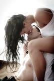 Das junge attraktive Paar, das draußen auf Strand küsst, schaukelt Stockfoto