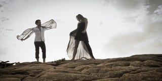 Das junge attraktive Paar, das draußen auf Strand tanzt, schaukelt stockfoto