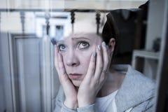 Das junge attraktive unglückliche deprimierte einsame Frauendenken sorgte sich durch das Fenster zu Hause Lizenzfreies Stockbild