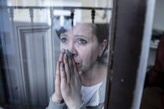 Das junge attraktive unglückliche deprimierte einsame Frauenschauen sorgte sich durch das Fenster zu Hause Lizenzfreies Stockbild