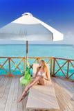 Das junge blonde Ein Sonnenbad nehmen gegen den tropischen Ozean Stockfotografie