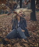 Das junge blonde Mädchen, das sie rüttelt, hed im Herbstlaub Stockfotografie
