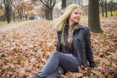 Das junge blonde Mädchen, das sie rüttelt, hed im Herbstlaub Lizenzfreie Stockfotos
