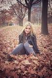 Das junge blonde Mädchen, das sie rüttelt, hed im Herbstlaub Lizenzfreies Stockfoto
