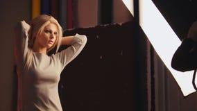 Das junge blonde weibliche Modell, das für Fotografen aufwirft - arbeiten Sie Bühne hinter dem Vorhang um Lizenzfreies Stockfoto