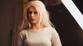 Das junge blonde weibliche Modell, das für Fotografen aufwirft - arbeiten Sie Bühne hinter dem Vorhang um Lizenzfreies Stockbild