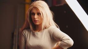 Das junge blonde weibliche Modell, das für Fotografen aufwirft - arbeiten Sie die Bühne hinter dem Vorhang um, horizontal Lizenzfreies Stockbild