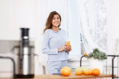 Das junge brunette Mädchen, das im hellblauen Pyjama gekleidet wird, steht mit Glas frischem Saft nahe bei dem Fenster im Licht lizenzfreies stockbild