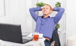 Das junge Geschäftsmannsitzen entspannte sich mit den Händen hinter seinem Kopf, dem Träumen, dem Denken oder dem Stillstehen Stockfoto