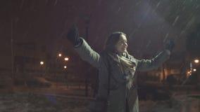 Das junge glückliche Mädchen genießt den fallenden Schnee seine Hände halten stock video footage