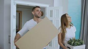 Das junge glückliche Paar, das in neues Haus nach Verlegung geht und küssen sich stock video footage