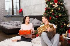 Das junge glückliche Paar in den Pyjamas lachend und freuen sich an ihren pres Lizenzfreie Stockfotos