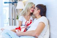Das junge glückliche Paar, das im Bett, hispanischer Mann liegt, geben Frauen-Überraschungs-Geschenk-Umschlag mit Band, Jahrestag Stockbilder