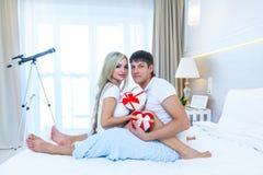 Das junge glückliche Paar, das im Bett, hispanischer Mann liegt, geben Frauen-Überraschungs-Geschenk-Umschlag mit Band, Jahrestag Stockbild