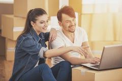 Das junge glückliche Paar, das nach Wohnungen mit Laptop sucht Bewegen, Kauf der neuen Wohnung stockfotografie