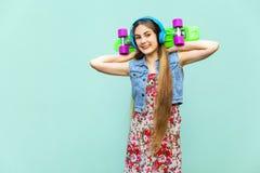 Das junge glückliche schöne langhaarige blonde Mädchen im Kleid und in den Kopfhörern, Spaß mit grünem Plastikpennyskateboard in  Lizenzfreie Stockbilder