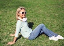 Das junge hübsche lächelnde Mädchen, das auf dem Gras sitzt, hört Musik Lizenzfreies Stockfoto