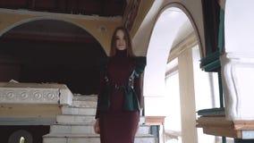 Das junge hübsche Mädchen, gekleidet in den ledernen Flügeln und in einem Lederrock, steigt die Treppe in einem verlassenen Gebäu stock video footage