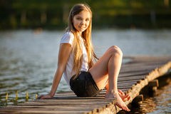 Das junge lächelnde Mädchen, das auf Pier im Sonnenuntergang sitzt, strahlt Stockfotografie