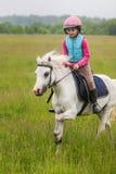 Das junge Mädchen auf einem Pferd, das über das Feld galoppiert Lizenzfreie Stockfotografie