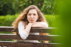 Das junge Mädchen, das auf einer Bank sitzt, machte und schaute lächerlich zu den Rahmen Lizenzfreie Stockbilder