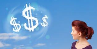 Das junge Mädchen, das auf Dollarzeichen zeigt, bewölkt sich auf blauem Himmel Lizenzfreie Stockfotografie