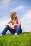 Das junge Mädchen, das auf einem grünen Gras sitzt Lizenzfreies Stockfoto