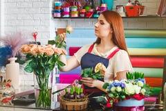 Das junge Mädchen, das in einem Blumenladen, Floristenfrau arbeitet, macht einen Blumenstrauß Stockfotografie