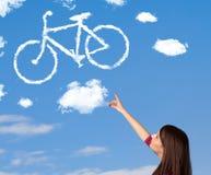 Das junge Mädchen, das Fahrrad betrachtet, bewölkt sich auf blauem Himmel Lizenzfreie Stockbilder