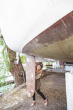 Das junge Mädchen, das hinter einem großen Kiel sich versteckt, yachts Stockbilder