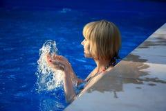 Das junge Mädchen, das im Pool mit lächelt, spritzt Stockbilder