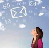 Das junge Mädchen, das Postsymbol betrachtet, bewölkt sich auf blauem Himmel Lizenzfreie Stockfotos
