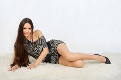 Das junge Mädchen, das striped Kleid trägt, liegt auf weißem Pelz Stockfotografie