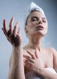 Das junge Mädchen, das Wasser genießt, spritzt auf ihrem Gesicht