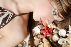 Das junge Mädchen im Bikini legt mit Seashells Lizenzfreie Stockbilder