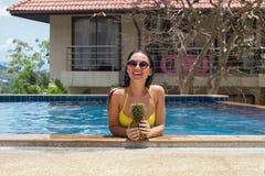 Das junge Mädchen im Pool mit Ananas in den Händen und in tragender Sonnenbrille eines glücklichen Lächelns und in einem gelben B lizenzfreies stockfoto