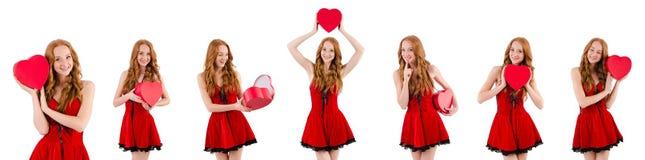 Das junge Mädchen im roten Kleid mit der Herzschatulle lokalisiert auf Weiß lizenzfreie stockfotografie