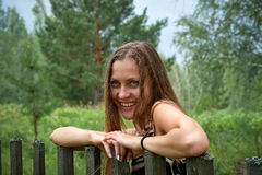 Das junge Mädchen lächelt an einem Bretterzaun stockfoto