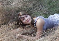 Das junge Mädchen liegt in einem Gras Lizenzfreie Stockfotos