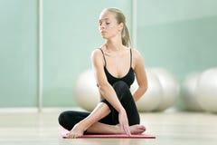 Das junge Mädchen meditiert im Sport zu einer Gymnastik Stockbilder