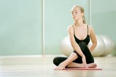 Das junge Mädchen meditiert im Sport zu einer Gymnastik Lizenzfreie Stockfotografie