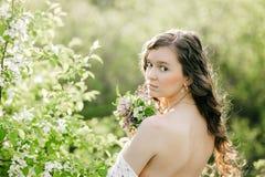 Das junge Mädchen mit einem Blumenstrauß von wilden Blumen Lizenzfreies Stockfoto
