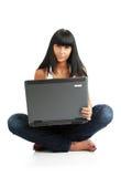 Das junge Mädchen mit einem Computer Lizenzfreie Stockfotos