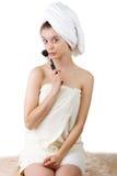 Das junge Mädchen nach einer Dusche in den Tüchern und mit Bürsten für ein Make-up Stockfotos