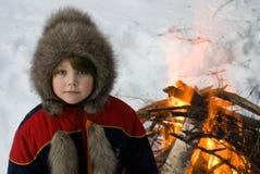 Das junge Mädchen nahe einem Feuer Stockbild