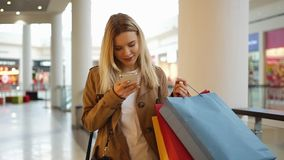 Das junge Mädchen schreibt etwas in ihrem Telefon gehend um das Mall mit Einkaufstaschen stock footage
