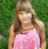 Das junge Mädchen sitzt auf den gras Lizenzfreie Stockfotos