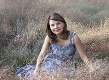 Das junge Mädchen sitzt im nicht schiefen Gras Lizenzfreie Stockfotos