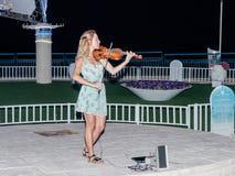 Das junge Mädchen am Sommerabend spielt für Passanten auf der Violine auf der Ufergegend von Naharija, Israel Lizenzfreie Stockfotografie