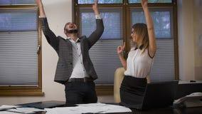 Das junge Mädchen und der Kerl im Büro Erfolgreiche Fertigstellung des Geschäfts durch das Internet, gehobene Stimmung und stock footage